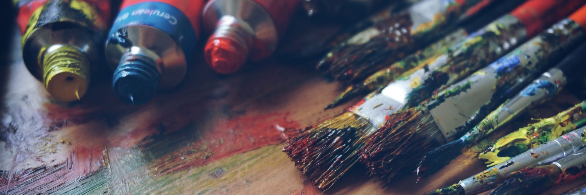 A rich pallette of freshly used paints and paintbrushes from a day of creating art