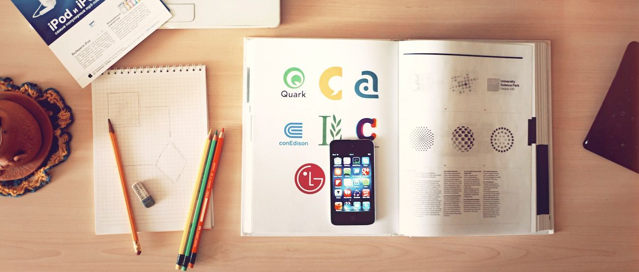 A collection of items that a designer would use on his desk including a notepad, pencils, a computer, an iphone and design books