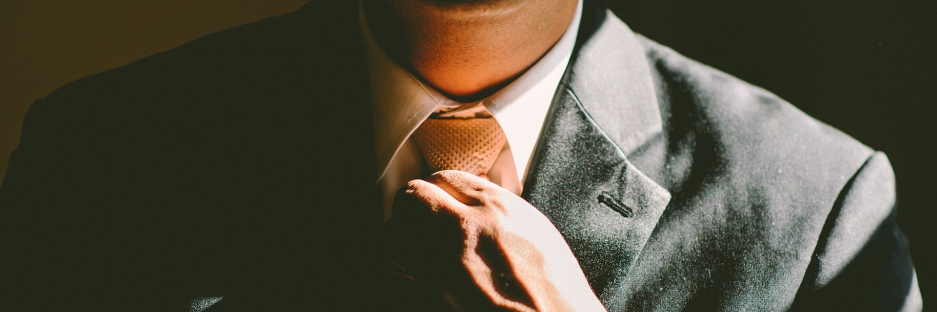 A person in a suit fixing his tie before going in to interview for a job in finance or consulting