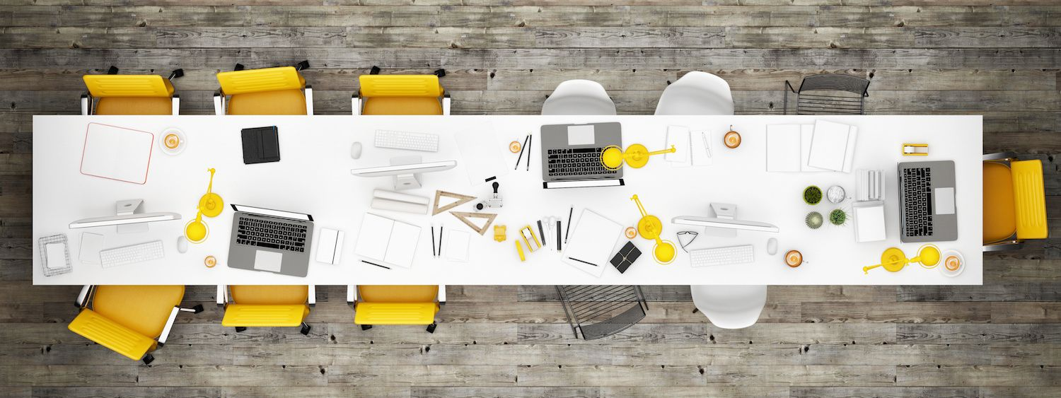 A creative work table in an open office plan typical of a design firm or an advertising agency with wide high resolution monitors and design instruments