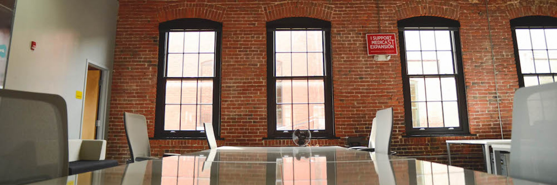 An exposed brick office as is typically occupied by startups in San Francisco and Brooklyn. This image depicts an empty conference room with a table and chairs prior to a meeting