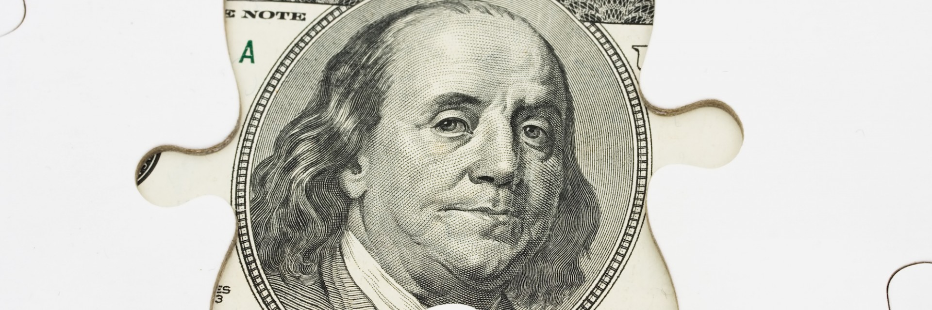 Ben Franklin on a $20 note covered by jigsaw pieces