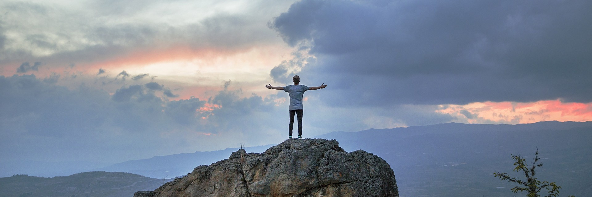 Man in t-shirt standing triumphantly after reaching the top of a big boulder during early sunrise in a national park