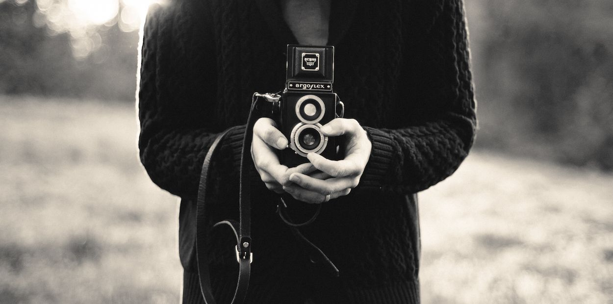 Man with vintage camera pointed towards the camera