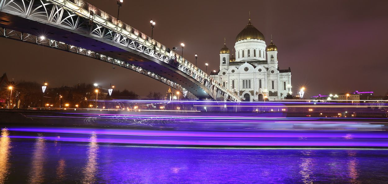 A beautiful newly constructed bridge lit up at night against the backdrop of an older illuminated building
