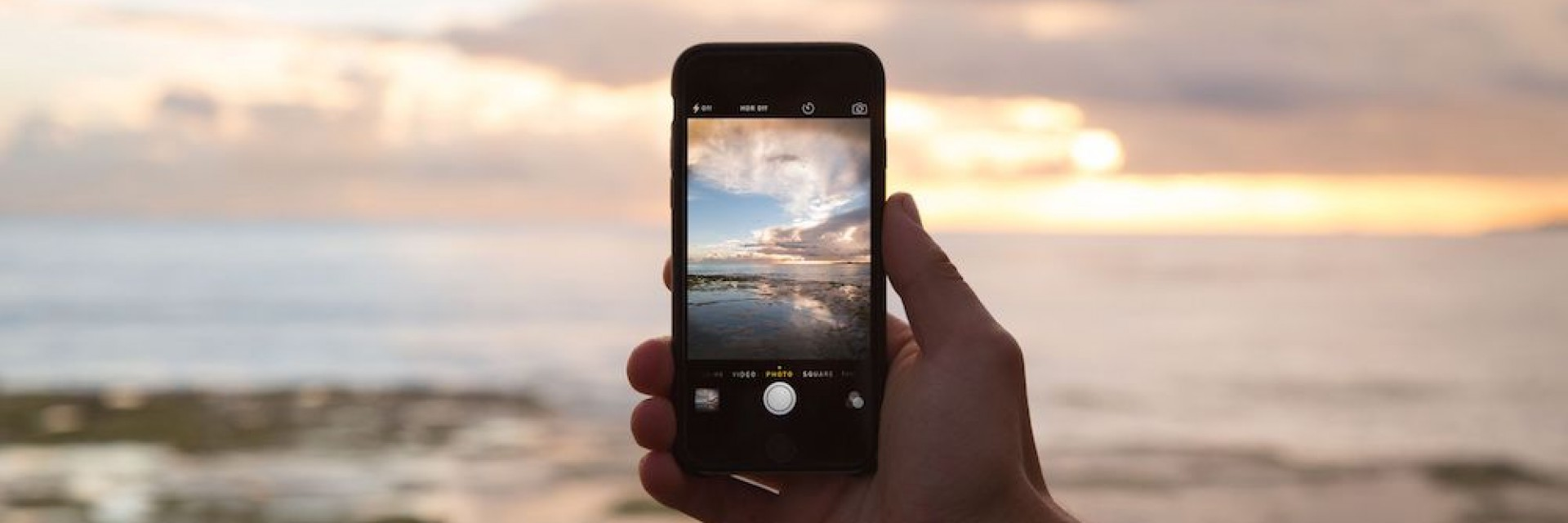 A man photographing a beautiful sunset on his smart phone