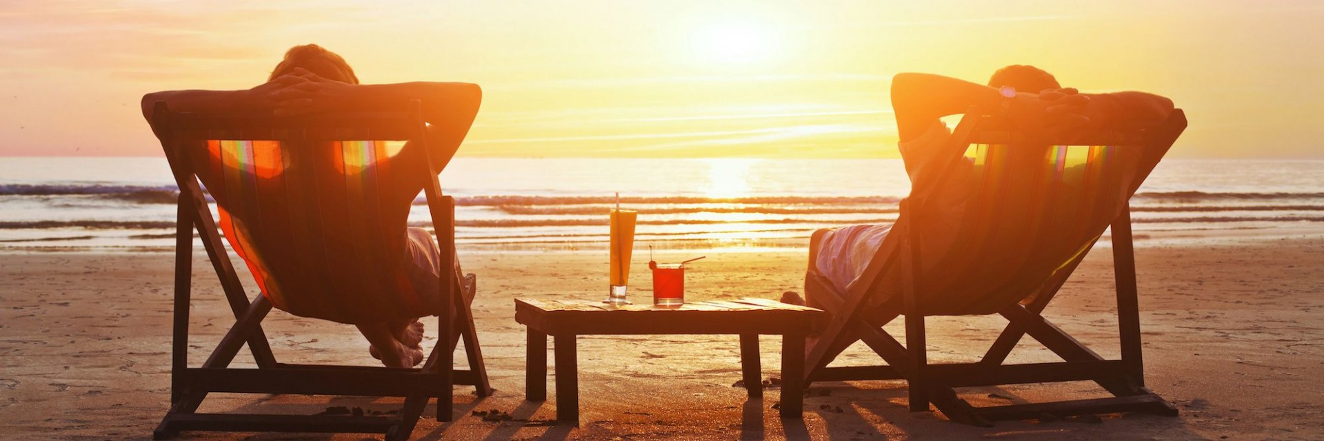 A couple sitting on a beach in front of a beautiful sunset on their vacation. Cocktail glasses between them