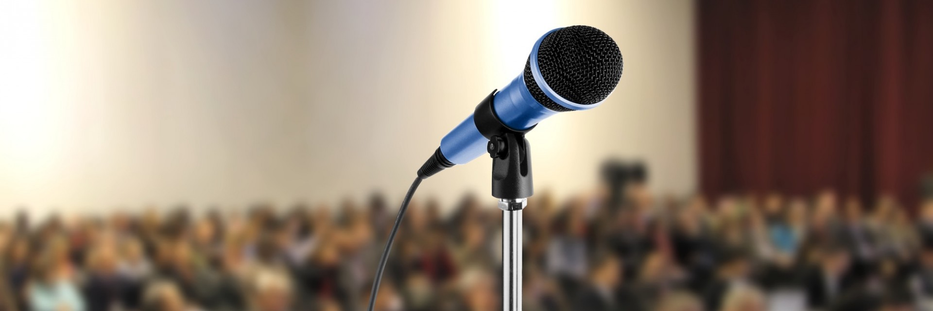 Microphone placed at a developer conference in front of a packed auditorium of attendees prior to a keynote speech