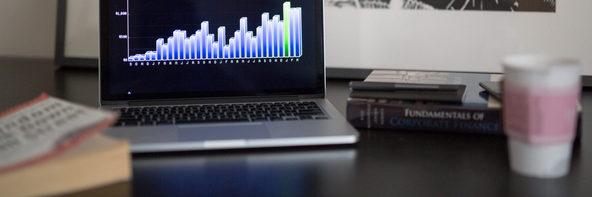 a laptop on a desk with pretty charts and visualization next to a couple of books and a coffee cup